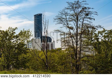 Wroclaw, Poland - May 8 2020: Top Of Sky Tower Skyscraper Behind Bushes Trees And Buildings