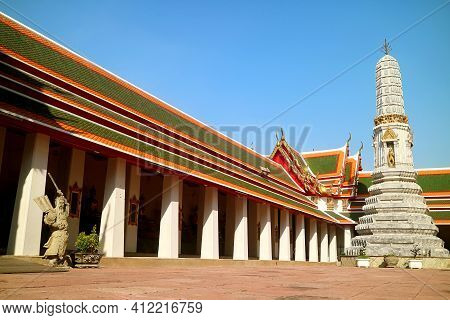 Cloister Of Wat Pho Temple With Phra Prang Pagoda And Chinese Guardian Statue Used As Ballast Stones