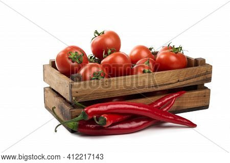A Wooden Old Box Full Of Fresh Juicy Red Tomatoes With Red Hot Chili Peppers