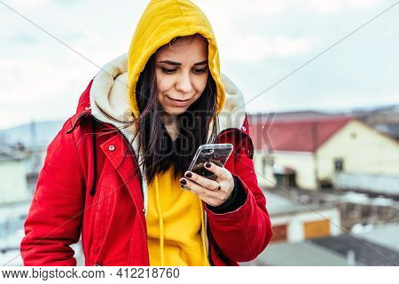 Portrait Of Young Woman With Mobile Phone On Roof Of Building. Brunette In Yellow Hoodie And Red Jac