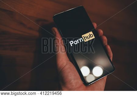Man Holding A Smartphone With Pornhub Logo On The Black Screen