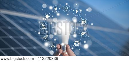The Man Holds A Light Bulb, Led Bulb On A Background Of Solar Panels With Icons Energy Sources For R