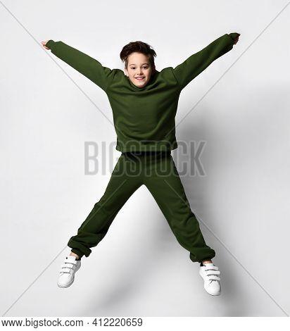 Happy Child Fashion Boy In Fashionable Warm Tracksuit Suit Bounces Isolated On Studio Background. Sc