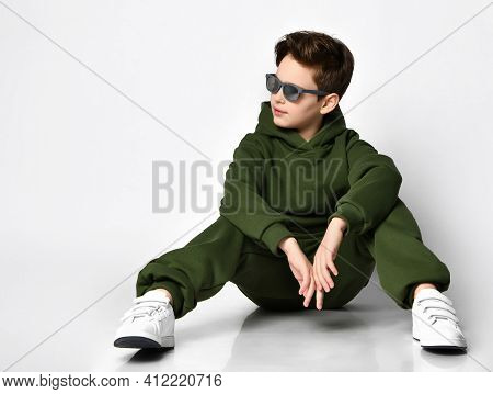 Cool Schoolboy In A Green Warm Fleece Tracksuit And Sunglasses Sitting On A Gray Background. Child L