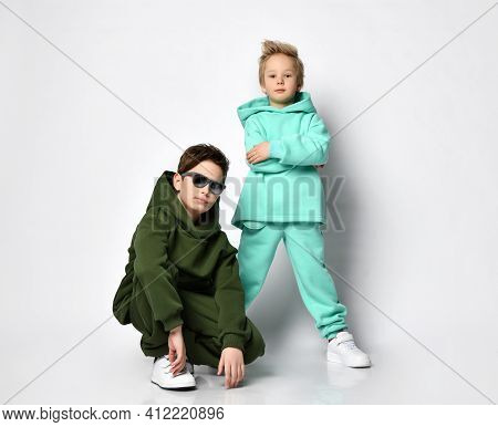 Two Bro Boys In Warm Suits In A Sports Style Are Posing On A Gray Background. Children Are Having Fu