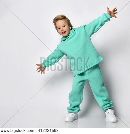 Happy Cute Blond Boy In A Warm Turquoise Suit On A Gray Background. A Child In Comfortable And Styli