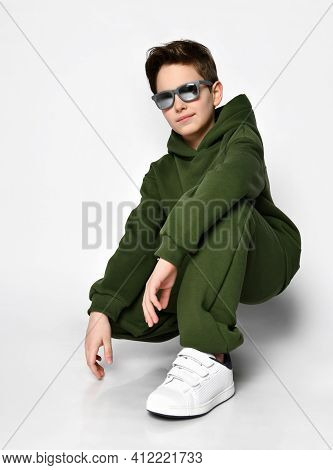 Cool Schoolboy In A Green Warm Fleece Tracksuit And Sunglasses Is Squatting On A Gray Background. Th