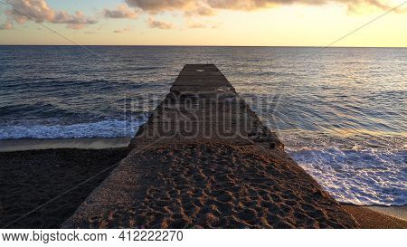 Old Concrete Pier On The Seashore At Sunset. Light Wind And Ripples On The Sea. The Concept Of Calm