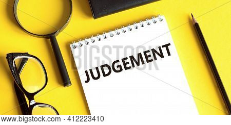 Notepad With The Text Judgement On A Yellow Background With Glasses, A Magnifying Glass And A Pencil