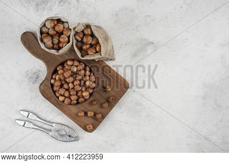Bowl Of Organic Hazelnut Kernels On Cutting Board With Shelled Hazelnuts