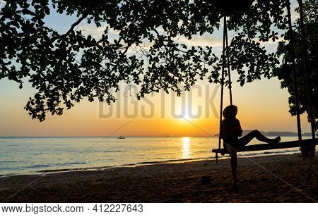 Woman on a swing at the beach at sunset