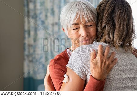 Close up of senior mother embracing adult daughter after covid-19 vaccination shot. Happy old grandmother and granddaughter meeting each other at the injection of the covid19 vaccine from virus.