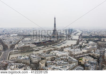 View on Eiffel tower and the river over the roofs of Paris on a grey cloudy day