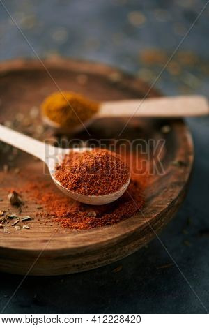 closeup of a wooden spoon full of red curry powder next to another wooden spoon full of regular curry powder, on a wooden plate, placed on a dark stone surface