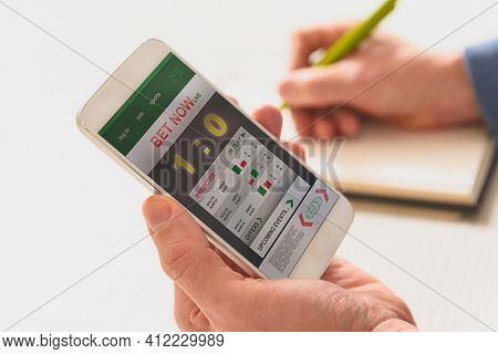 Betting on sports, holding smart phone with working online betting mobile application