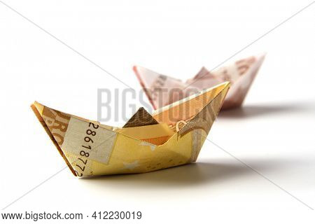 Paper boats folded from European Euro currency bills on white background