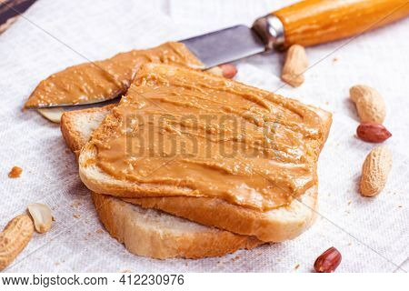 Homemade Toasts  For Breakfast With Fresh Crunchy Peanut Butter And Nuts On Light Textile Background