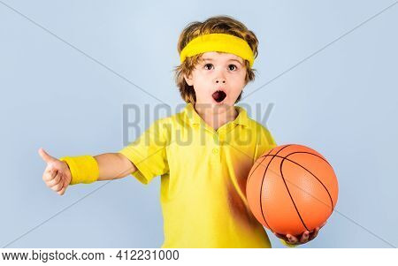 Children And Sport. Little Basketballer In Sportswear With Ball. Small Boy In Sport Uniform Playing