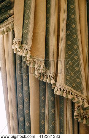 Expensive Green And Gold Curtains With Bells Close Up. Floral Fringed Curtains At The Hotel.