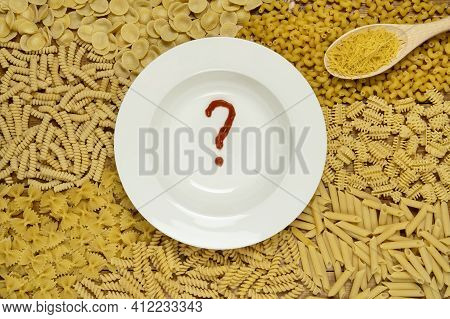 Empty Plate With Catsup Question Mark On Background From Assortment Of Italian Pasta.