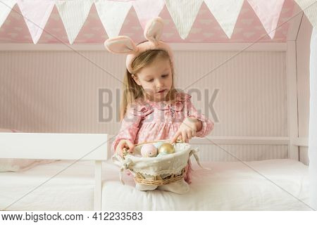 Little Girl Wearing Bunny Ears And Holding A Basket Of Easter Eggs. Happy Easter. Preparing Family F