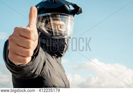 Motorcyclist Wearing A Black Dual-purpose Motorcycle Helmet With A Black Jacket With Sky Background
