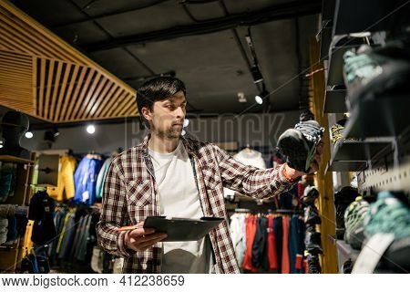 Sales Assistant Sports Travel Store Makes Inventory Hiking Boots. Travel Goods Store Theme. Clothes