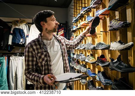 Sporting Goods Store Owner With Clipboard Checking Inventory. Tourist Store Manager Working Near Sho