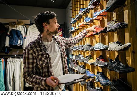 Business Owner In Sports Store Works With Showcase Trekking And Mountaineering Boots For Sale, Holdi