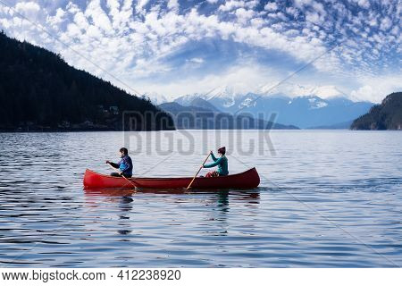 Couple Friends Canoeing On A Wooden Canoe