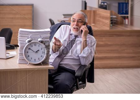 Old male employee in time manegement concept