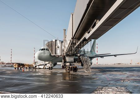 The Passenger Jet Plane Stands At The Air Bridge On An Airport Apron. The Baggage Is Being Loaded