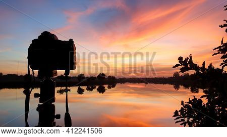 Silhouette Of A Camera At Sunset.dslr Camera Shooting On A Cityscape Sunset With Lake Reflection.