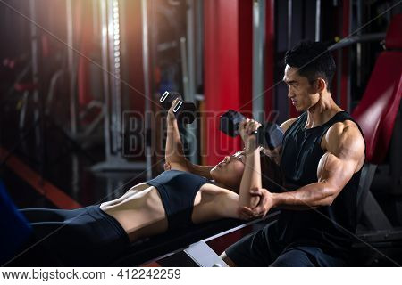 Personal Fitness Trainer Helping Woman Practice Dumbbells. Personal Trainer In Fitness Gym