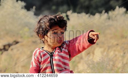 A Little Boy Of Indian Origin Is Seen Looking Away From His Finger And Hand. Concept For Today's Chi