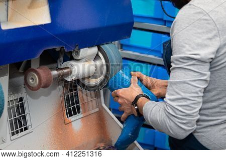 Male Person Working On A Grinding Machine In A Showmaker Factory. Professional Worker Employed In A