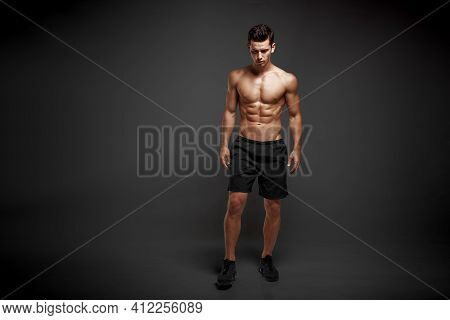 Full Length Image Of A Strong Athletic Man Showing Muscular Body And Sixpack Abs Isolated Black Back