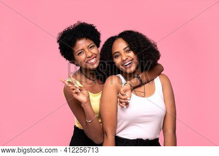 Two Beautiful Female Friends Having Fun Together In Studio. Afro Women Posing On Pink Pastel Backgro