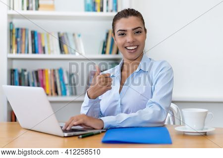 Laughing Latin American Business Trainee Working At Computer At Desk At Office
