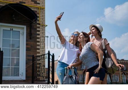 Three Happy Girls Friends Go On A Trip And Take A Selfie On A Mobile Phone. The Blonde Brunette And