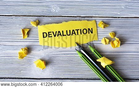 Devaluation - Word On A Yellow Tattered Piece Of Paper With Pencils And Crumpled Paper Lumps On A Li