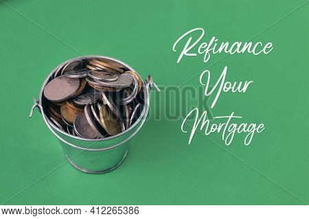 Coins Over Green Background Written With Refinance Your Mortgage