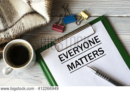 Everyone Matters - Text In A Notebook With A Pen, A Cactus, A Cup Of Coffee And A Fragment Of A Brow