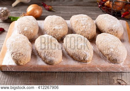 Frozen Cutlets Lie On A Wooden Board. Raw Meat Semi-finished Products Are Ready For Cooking