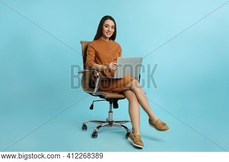 Young Woman With Laptop Sitting In Comfortable Office Chair On Turquoise Background