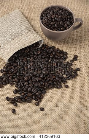Bunch Of Medium Roasted Coffee Beans Out Of Sackcloth On Marble Surface