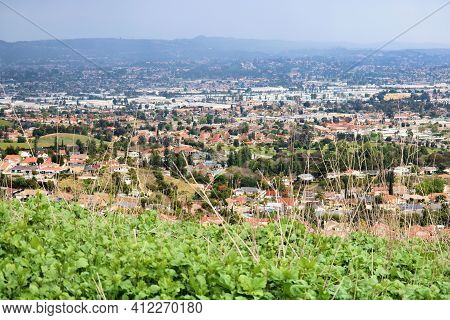 Urban Sprawl Encroaching On A Rural Hillside With Lush Grasslands At A Grassy Field Taken In The Pue