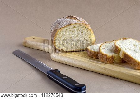 Sliced Fresh Bread Loaf On Cutting Board. Baked Bread And Knife Lies On Table On Craft Paper, Home B