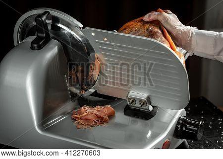 Slicing Hamon On Cutting Machine. Iberian Ham Cutter On Black Background.