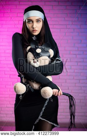 A Woman In A Sexy Nun Costume With A Teddy Bear Dressed In Accessories For Bdsm Games